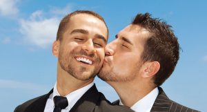 A man kisses his male partner on the cheek